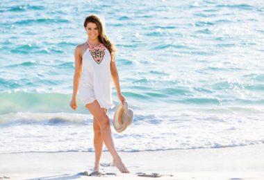 Portrait of young pretty woman walking along sandy beach